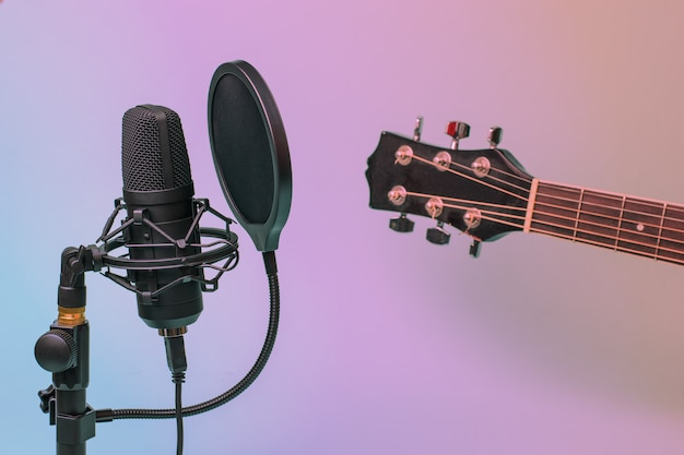Przyciemniany obraz gryfu gitary i nowoczesnego mikrofonu