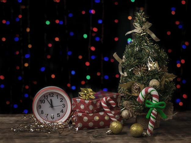 Przyciemniany obraz ze świerkiem, zegarem i prezentami. obchody nowego roku.