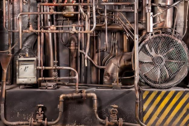 Przyciemniona migawka starego industrialnego wnętrza hali fabrycznej z rurami i mediami