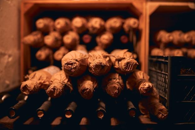 Przyciemniona piwnica winiarska z wykwintnym winem w butelkach zawiniętych w papier i umieszczonych na półkach