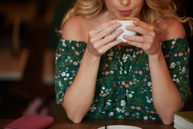 Przycięta blondynka popija cappuccino z kubka