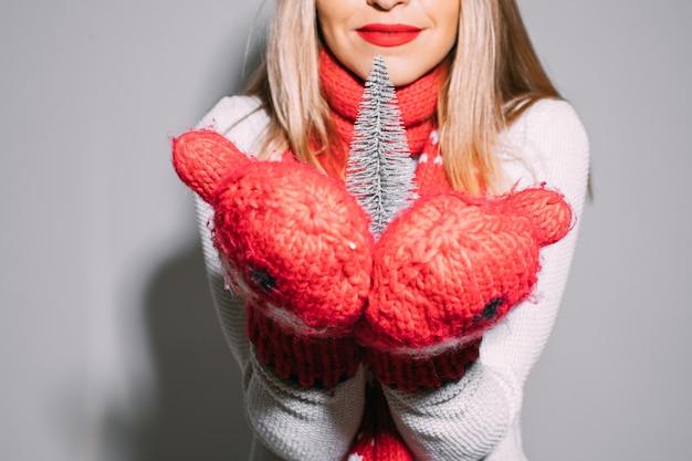 Przycięta blondynka z czerwonymi ustami, trzymając drobny symbol choinki w czerwonych rękawiczkach z dzianiny.