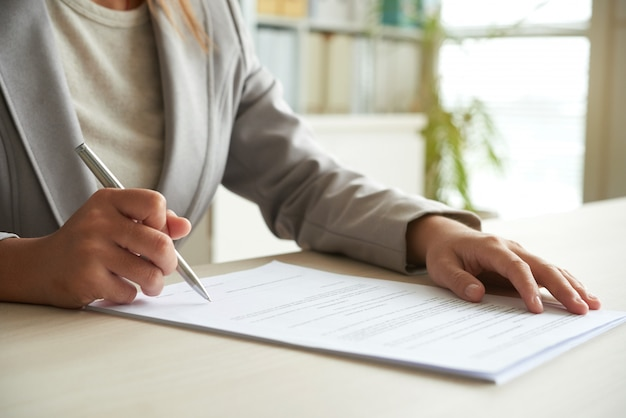 Przycięta część środkowa nierozpoznawalnej kobiety podpisującej dokument