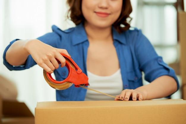 Przycięta kobieta zamykająca pudełko taśmą klejącą