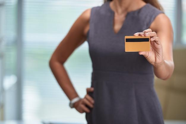 Przycięta nierozpoznawalna kobieta trzyma kartę bankową