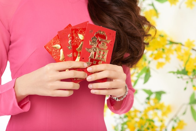 Przycięta nierozpoznawalna kobieta trzyma karty podarunkowe chiński nowy rok