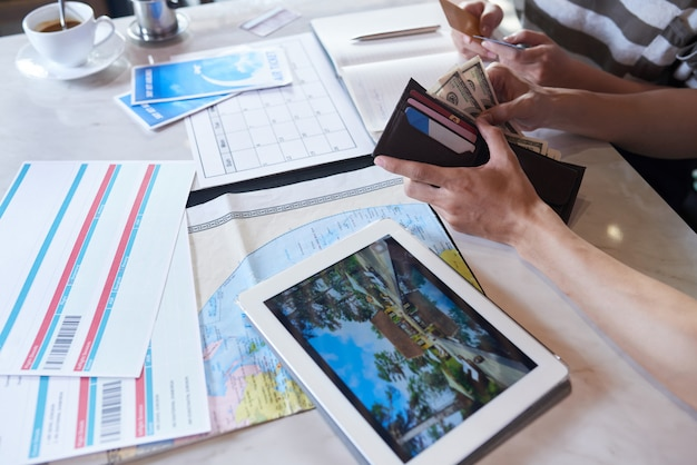Przycięta nierozpoznawalna para liczy pieniądze na wakacje