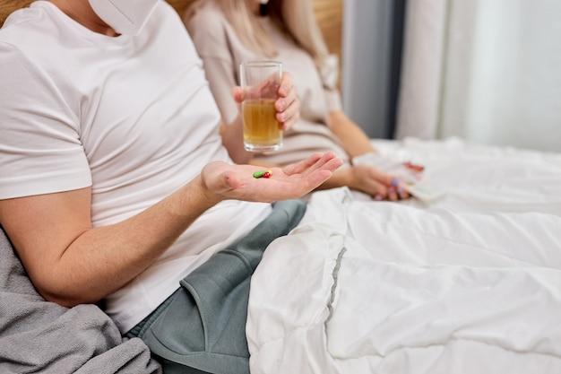 Przycięta para w domu z chorobą sezonową zimową przeziębienie leży w łóżku, bierze leki, wspiera się i pomaga sobie nawzajem w domu. koronawirus, covid-19, pojęcie choroby