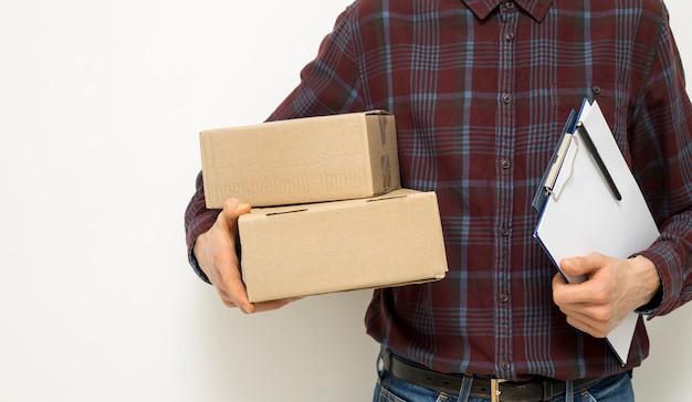 Przycięta rama kuriera dostawy na białym tle z pudełkami w ręku.