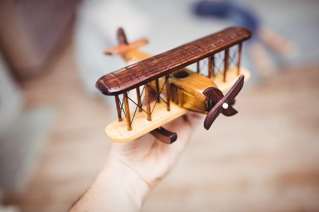 Przycięta ręka bawić się z drewnianym samolotem