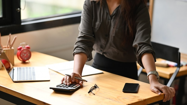 Przycięta strzał kobieta obliczyć pieniężne na kalkulatorze.