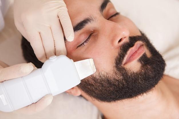 Przycięte bliska mężczyzny klienta uzyskiwanie oczyszczania ultradźwiękowego w salonie kosmetycznym