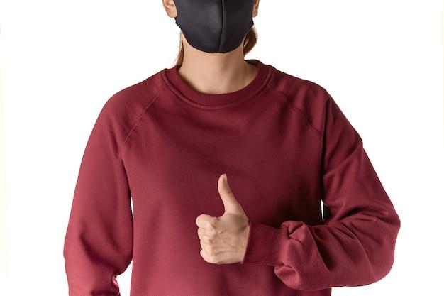 Przycięte bliska strzał młodej kobiety europejskiej noszącej maskę i bordową bluzę pokazując kciuk do góry