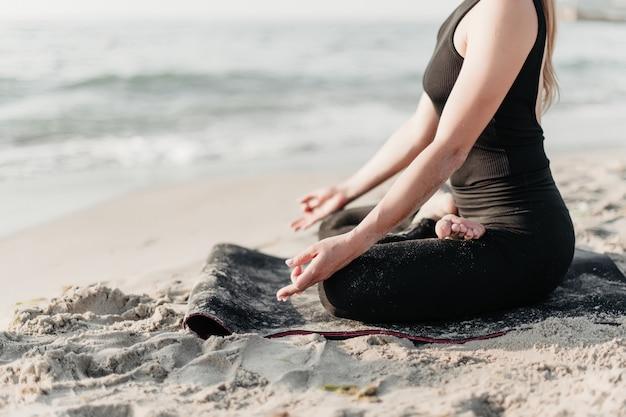 Przycięte ciało kobiety medytacji na plaży, siedząc na matę do jogi w relaksującej pozie