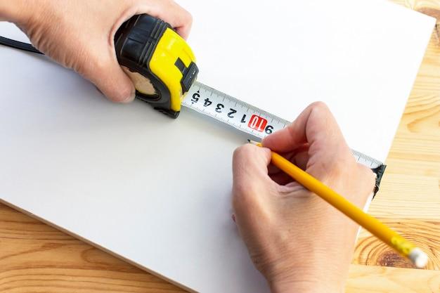 Przycięte dłonie cieśli zaznaczające biały drewniany panel żółtym ołówkiem i linijką