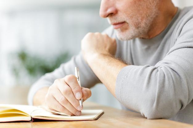 Przycięte dojrzały starszy biznesmen siedzieć w kawiarni pisząc notatki w notatniku.