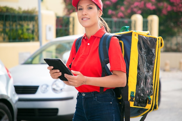 Przycięte kobiece kurier i trzymając tablet. profesjonalna dostawa kobieta w czerwonej czapce i koszuli, niosąca żółtą torbę termiczną i uśmiechnięta. dostawa i koncepcja zakupów online