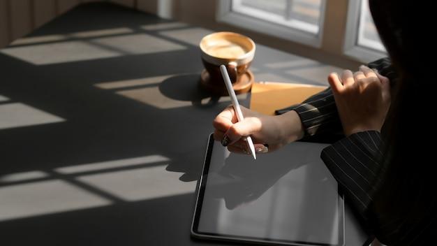 Przycięte kobiece pisanie na cyfrowym tablecie w ciemnym nowoczesnym miejscu pracy