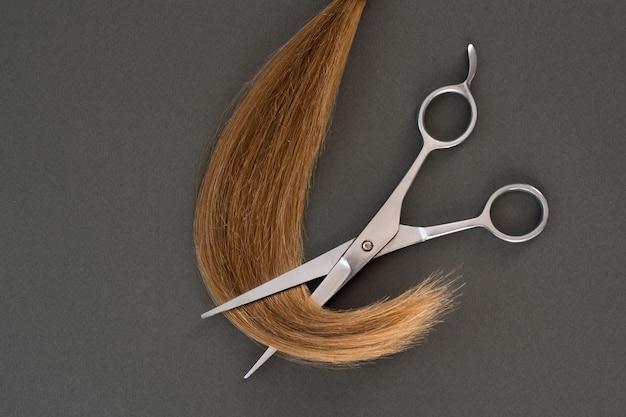 Przycięte loki blondynów i nożyczek. czarne tło. zbliżenie