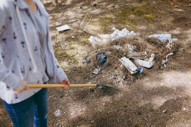 Przycięte młoda kobieta w zwykłych ubraniach czyści śmieci za pomocą grabi do zbierania śmieci w zaśmieconym parku