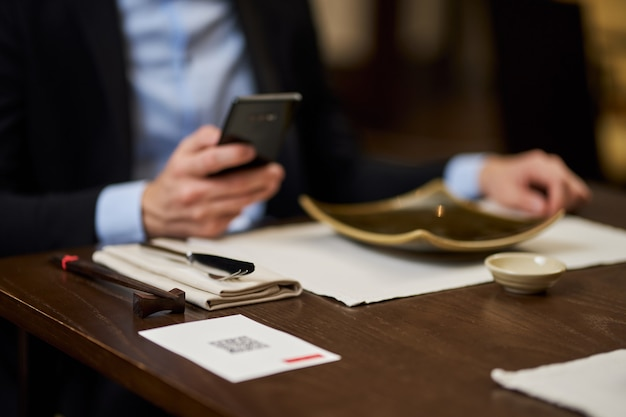 Przycięte niewyraźne zdjęcie mężczyzny w garniturze, trzymającego smartfona siedzącego przy stole w restauracji