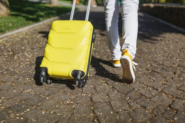 Przycięte nogi w żółtych trampkach w kroku, turysta kobieta w ubraniu z walizką stojącą, chodzenie po mieście na świeżym powietrzu. dziewczyna wyjeżdża za granicę na weekendowy wypad. koncepcja stylu życia turystyki