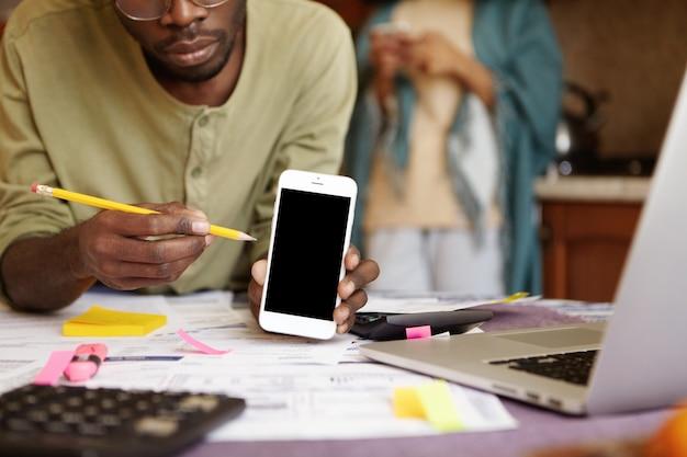 Przycięte portret african-american mężczyzna siedzi przy stole w kuchni z otwartym laptopem