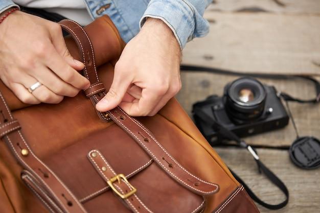 Przycięte przystojny fotograf męski w dłonie biorący aparat ze skórzanego ręcznie robionego plecaka, zamierzający robić zdjęcia. fotografia, koncepcja ręcznie robionych akcesoriów. kopiuj przestrzeń