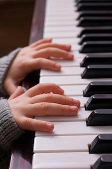 Przycięte ręce dziecka grającego na starym pianinie
