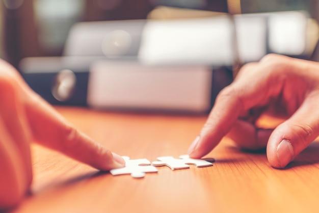 Przycięte ręce przedsiębiorców łączących kawałki układanki