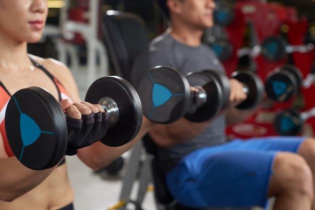 Przycięte sportowców wykonujących w dniu ramienia w siłowni