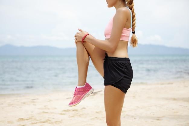 Przycięte strzał blondynka kaukaska z pięknym dopasowanym ciałem robi ćwiczenia rozciągające przed treningiem joggingu, stojąc na plaży przed niewyraźnym oceanem