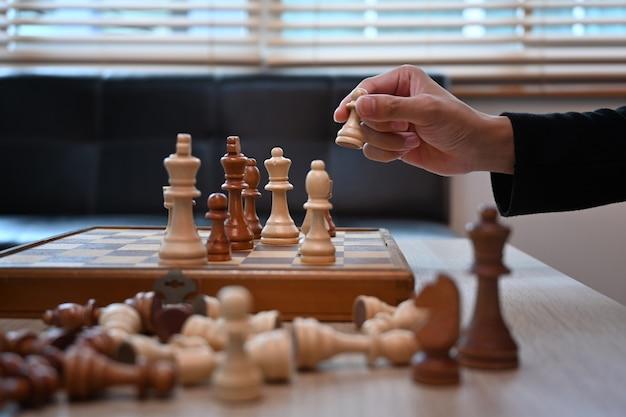 Przycięte strzał człowieka grającego w szachy w salonie.