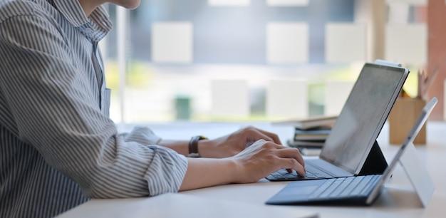 Przycięte strzał człowieka za pomocą laptopa i cyfrowego tabletu w nowoczesnym biurze.