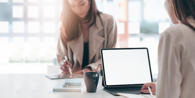 Przycięte strzał dwóch młodych businesswoman razem pracujących na komputerze typu tablet w nowoczesnym biurze.
