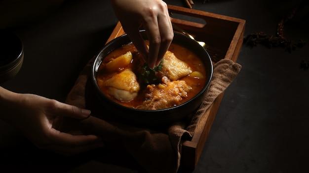 Przycięte strzał kobiecej dłoni gotowania kurczaka massaman curry służyć w restauracji tajskiej