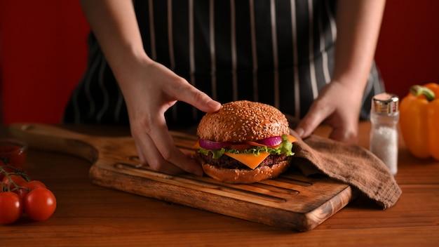 Przycięte strzał kobiety kucharz ręki trzymającej pyszne grillowane burgery wołowe miejsce na drewnianej tacy, aby służyć w restauracji