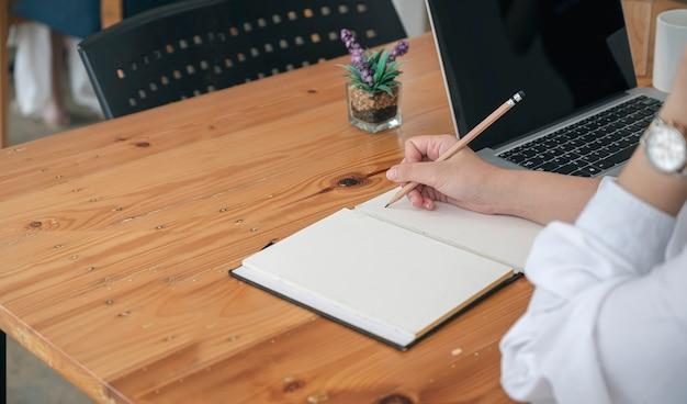 Przycięte strzał kobiety strony pisania na notebooku