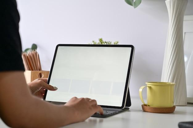 Przycięte strzał kreatywny projektant pracujący z nowoczesną tabletkę i klawiaturę na białym stole w obszarze roboczym studio