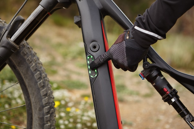 Przycięte strzał męskiej dłoni w czarnej rękawiczce naciskając przycisk z palcem wskazującym na panelu sterowania na rowerze elektrycznym. rowerzysta przełącza tryb prędkości przed jazdą na swoim silniku wspomagającym pod górę