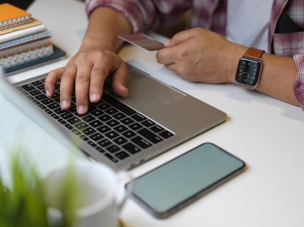 Przycięte strzał męskiej ręki wpisując na klawiaturze laptopa na stole roboczym ze smartfonem i papeterią