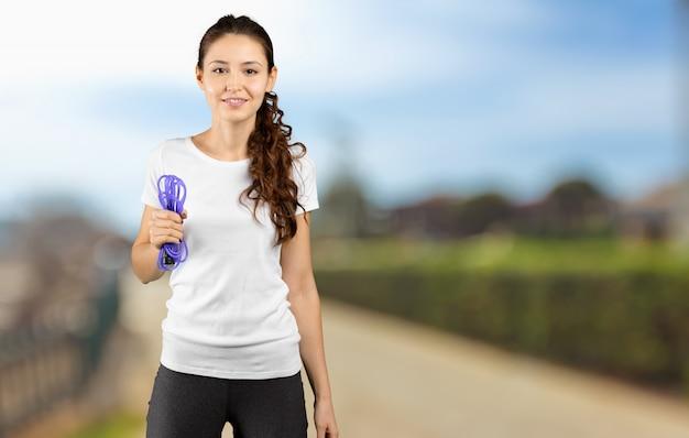 Przycięte strzał młoda kobieta sportowy gospodarstwa pomijam liny