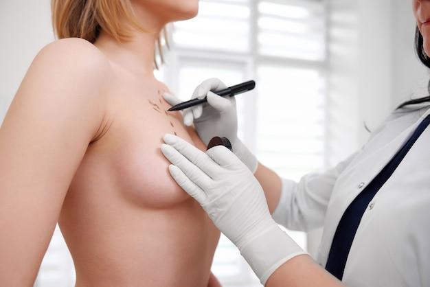 Przycięte strzał młodej kobiety wizyty u lekarza przygotowuje się do zabiegu powiększania piersi uroda zdrowie medycyna profesjonalizm koncepcja przygotowania chirurga.