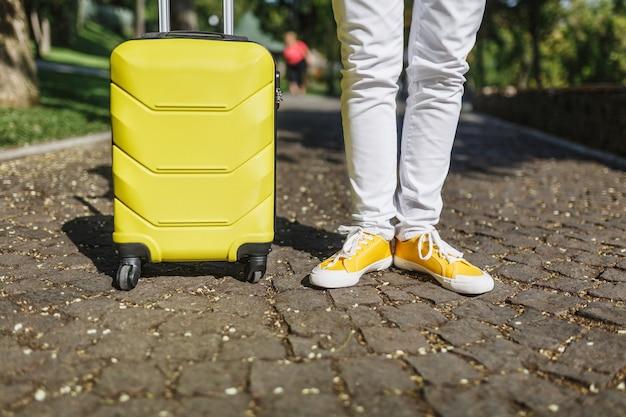 Przycięte strzał nogi w żółtych trampkach, turysta kobieta w ubraniu z walizką stojącą, chodzenie po mieście na świeżym powietrzu. dziewczyna wyjeżdża za granicę na weekendowy wypad. koncepcja stylu życia turystyki.