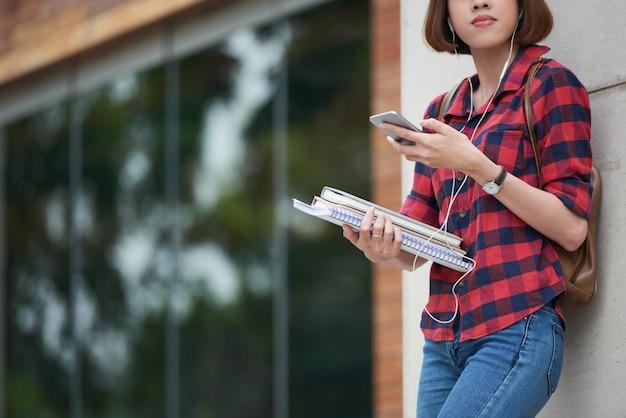 Przycięte studentki słuchania muzyki przed zajęciami na świeżym powietrzu