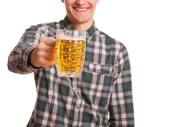Przycięte studio strzał szczęśliwego mężczyzny, uśmiechając się z radością wyciągając szklankę piwa do aparatu