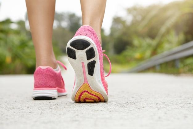 Przycięte tylne ujęcie lekkoatletycznej dziewczyny w różowych trampkach podczas wędrówki lub joggingu na chodniku na zewnątrz. kobieta jogger z dopasowanymi pięknymi nogami robi trening.