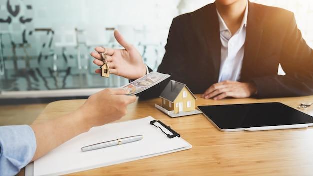 Przycięte ujęcie agenta nieruchomości, który daje klucz do domu swojemu klientowi