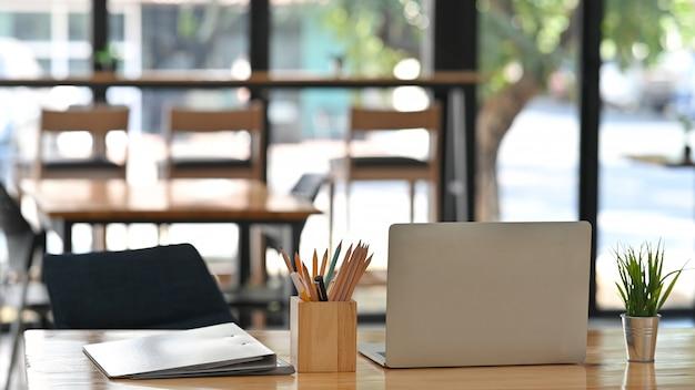 Przycięte ujęcie białego laptopa, ołówka, teczek dokumentów, rośliny doniczkowej na biurku.