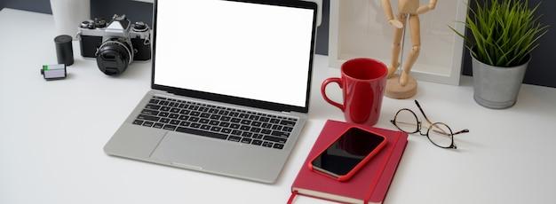 Przycięte ujęcie biurka z makietą laptopa, smartfona i materiałów biurowych